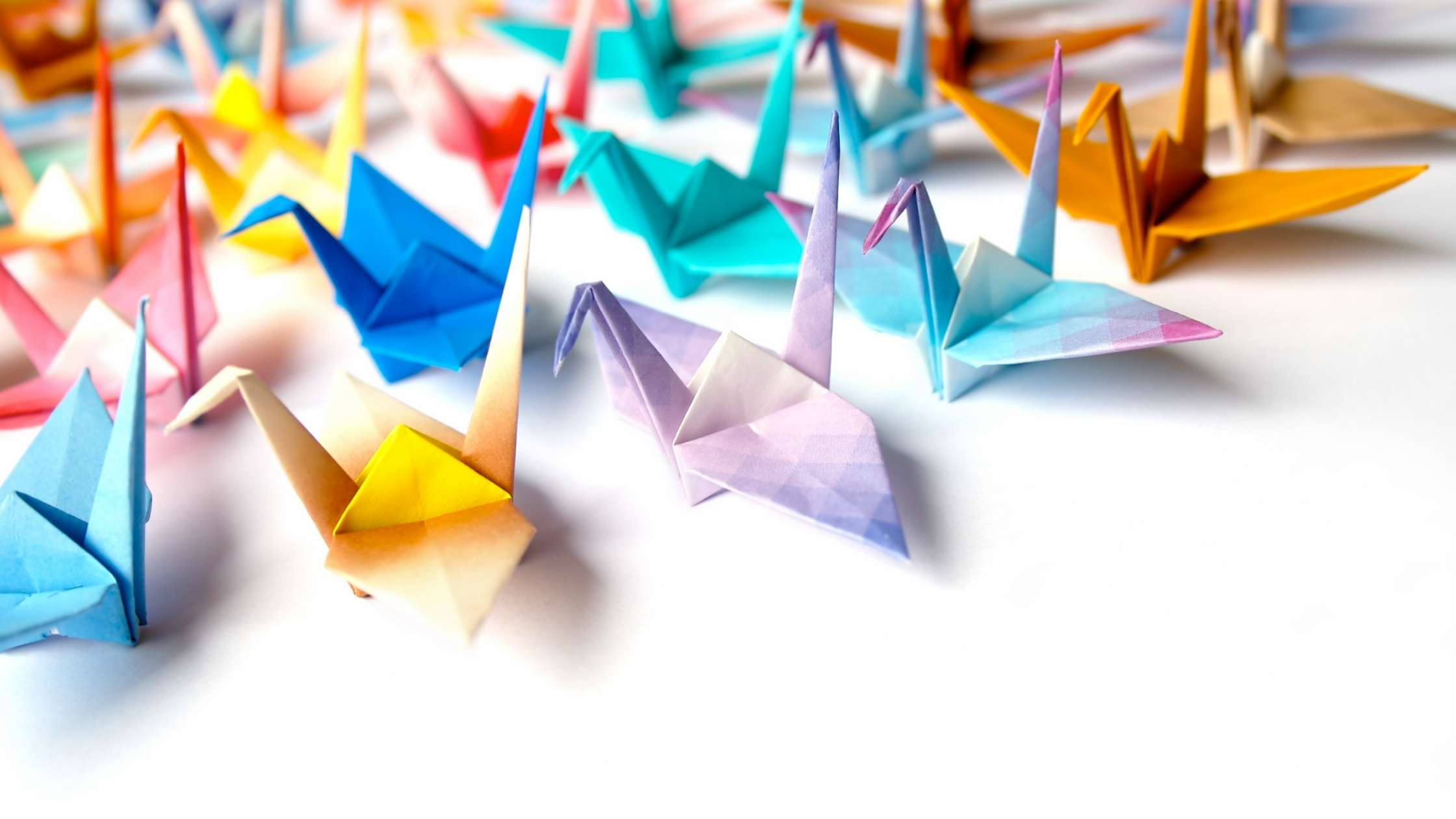 Flutter concept; collection of multicoloured origami paper cranes on a light background
