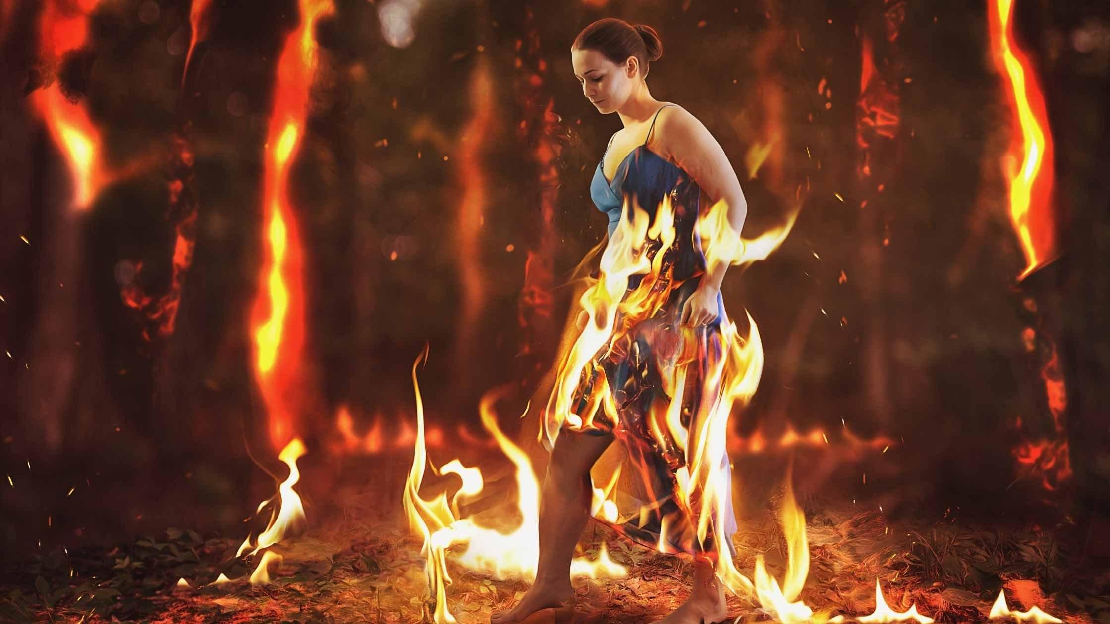 Woman walks through a burning forest fire