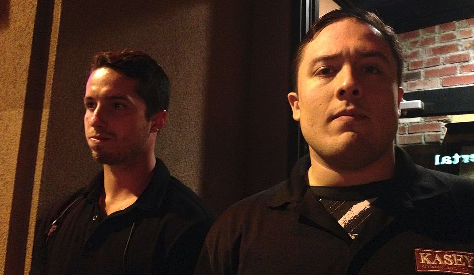 Security concept; Two young male bouncers outside a venue