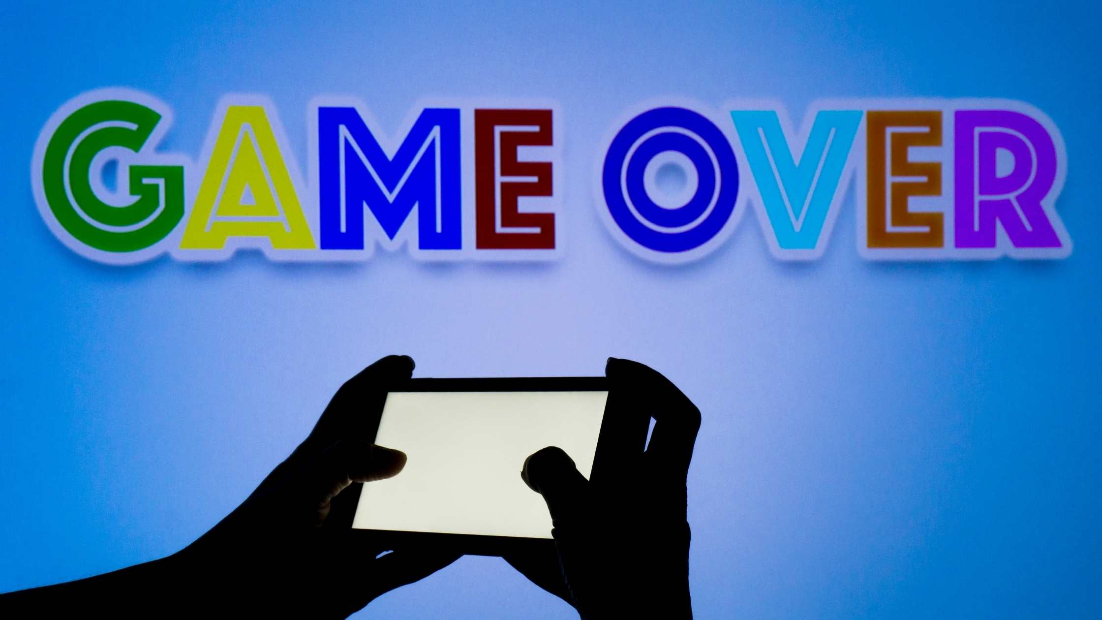 Mobile gaming concept; Close up of hands holding mobile phone; Colourful 'Game Over' text above