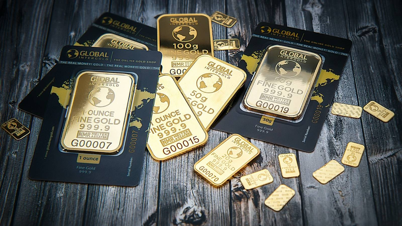 Gold bullion bars of various sizes on a wooden floor