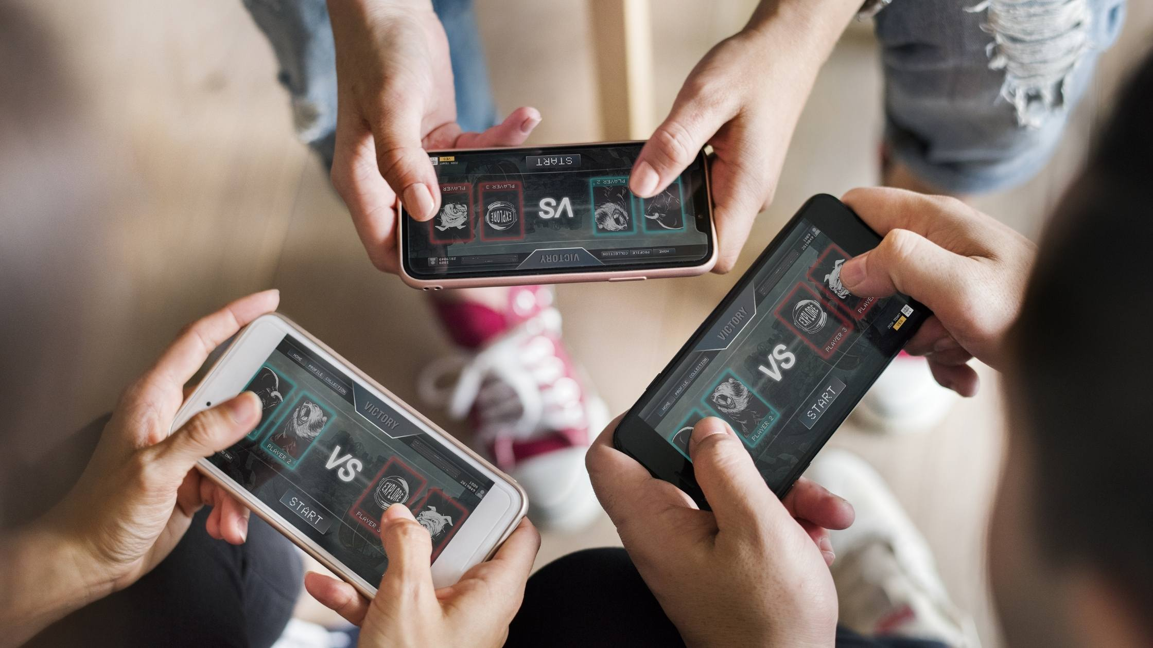 Close up of three people playing a game together on their mobile phones