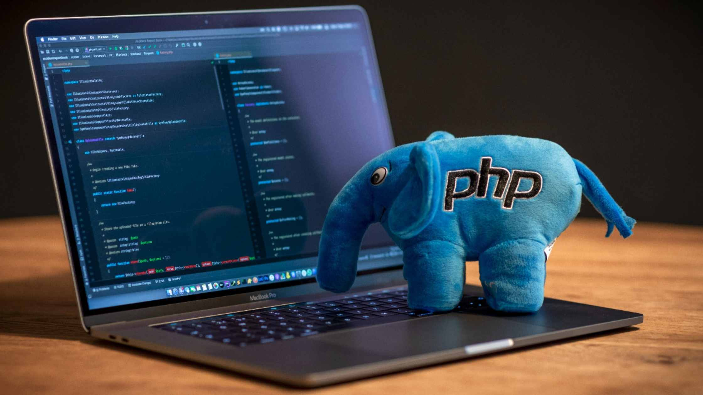 PHP programming concept; Blue plush elephant with embroidered PHP logo standing on laptop