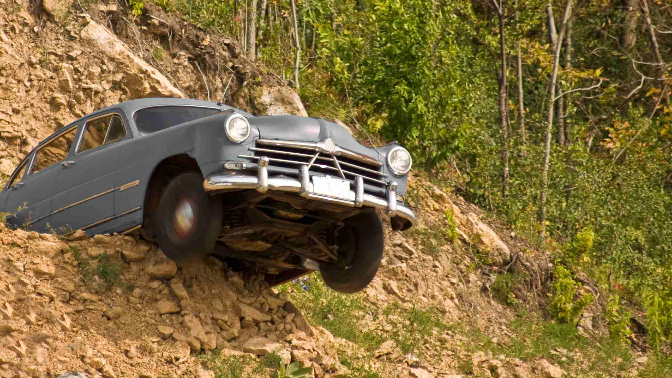 Tipping point concept; vintage car tipping over cliff edge