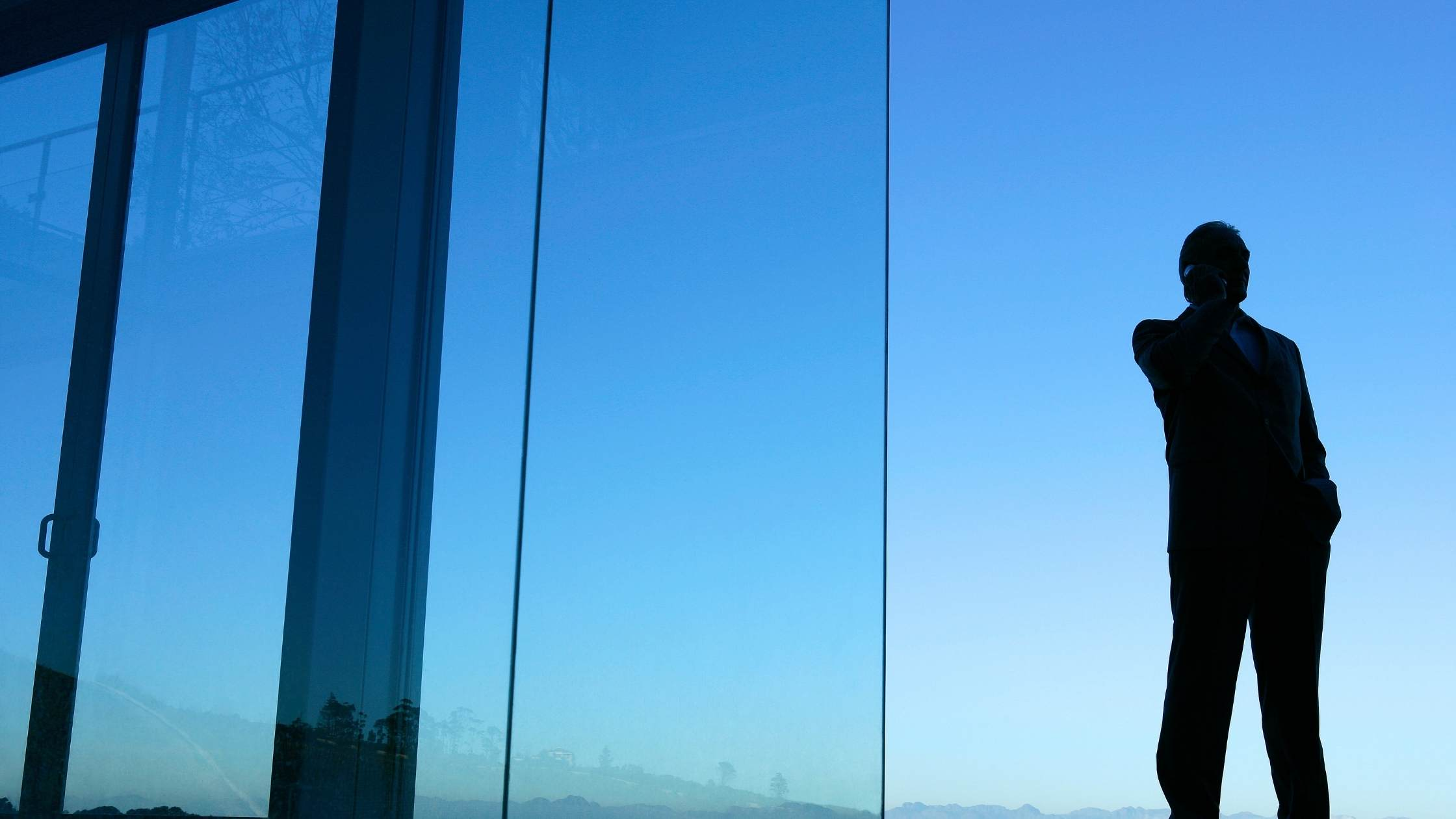 Silhouette of man talking on mobile phone in front of glass house