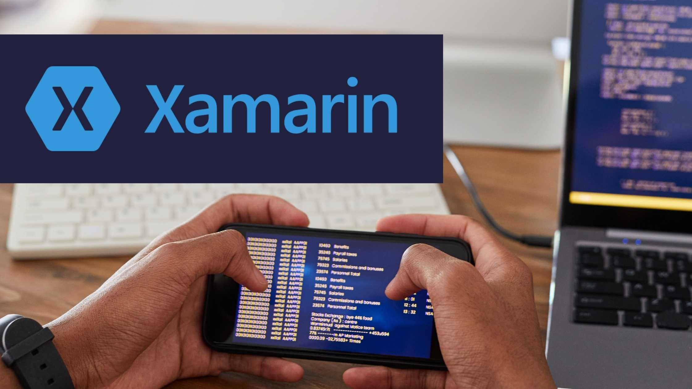 Close up of hands holding mobile phone; laptop and keyboard in background; Dark blue rectangle with Xamarin logo and text