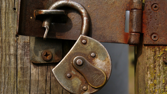 Security concept, rusty unlocked padlock on wooden gate