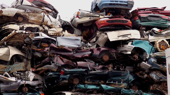 Car scrapyard, pile of crushed vehicles in junk yard